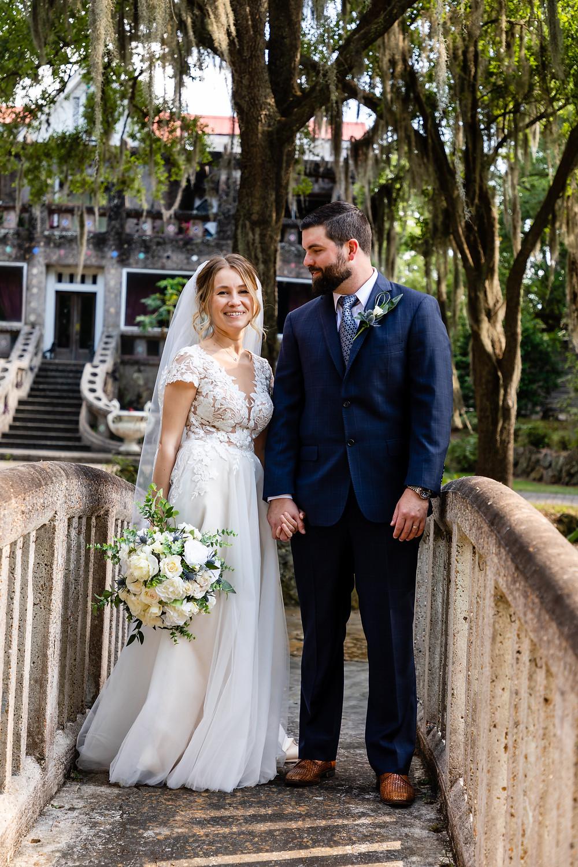 Cincinnatti wedding photographer captures image of bride and groom standing in stone bridge smiling to each other.