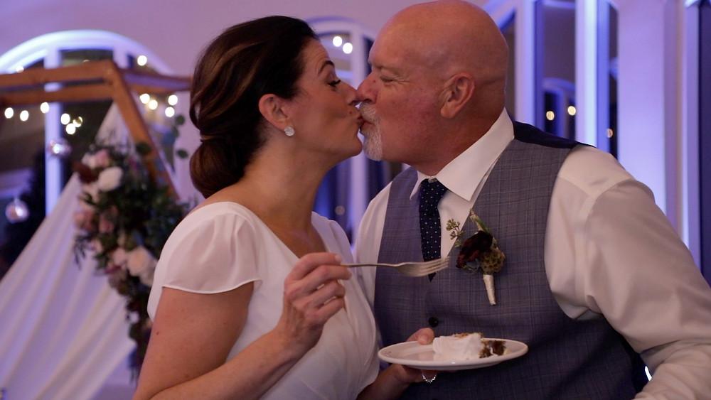 Cincinnati wedding photographer captures image of married couple kissing eating cake.