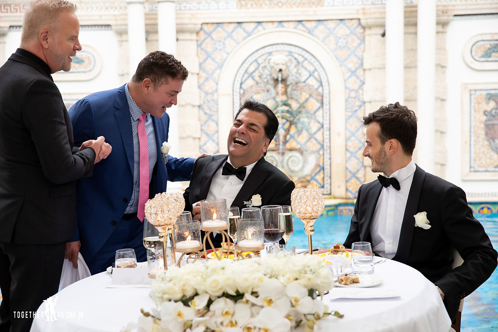 Groom laughs as best man talk at their wedding table