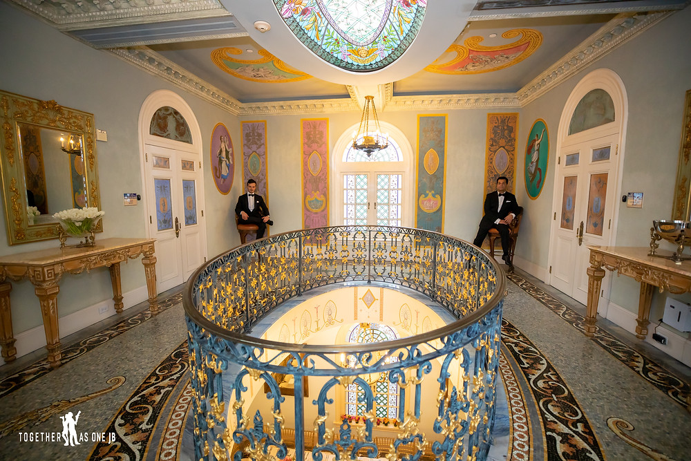 Groom sit in opposite corners of room where there is an oval opening to room below and a stained glass oval above