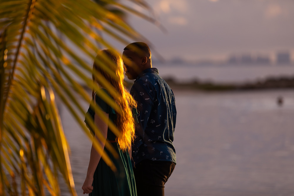 Miami wedding photographer captures image of couple walking on the beach behind palm tree.