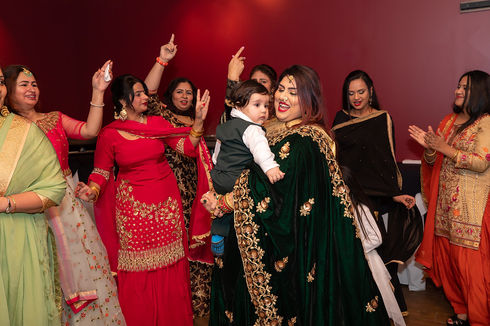 Indian birthday photographer captures image of indian women dancing together celebrating birthday.