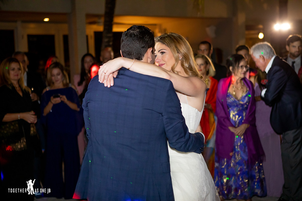 Bride and Groom dancing their first dance with wedding guests behind them during the wedding reception in the M Building in Wynwood