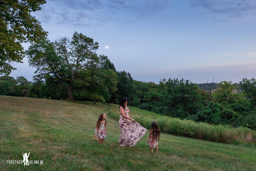 Family portrait photo of a mother and daughters dancing under the moon and the stars in Mount Snow Cincinnati.