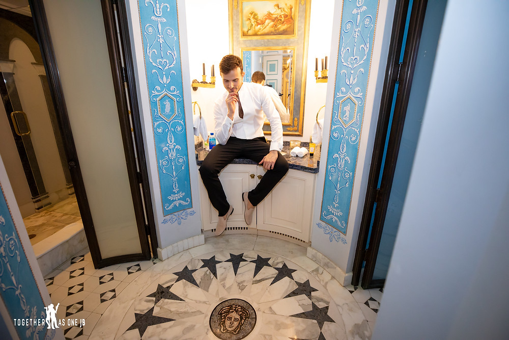Groom poses in bathroom and looks at Versace symbol on floor of beautiful bathroom at the former Versace Mansion