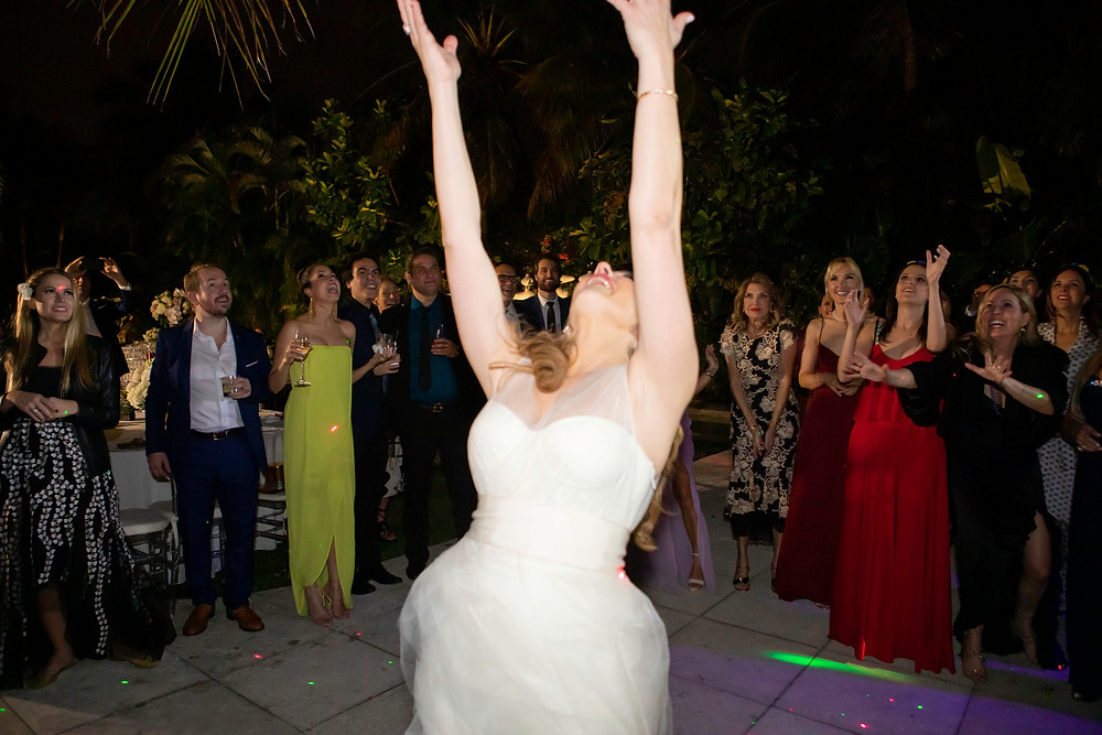 Bride throwing flowers at single ladies at wedding reception at the M Building in Wynwood