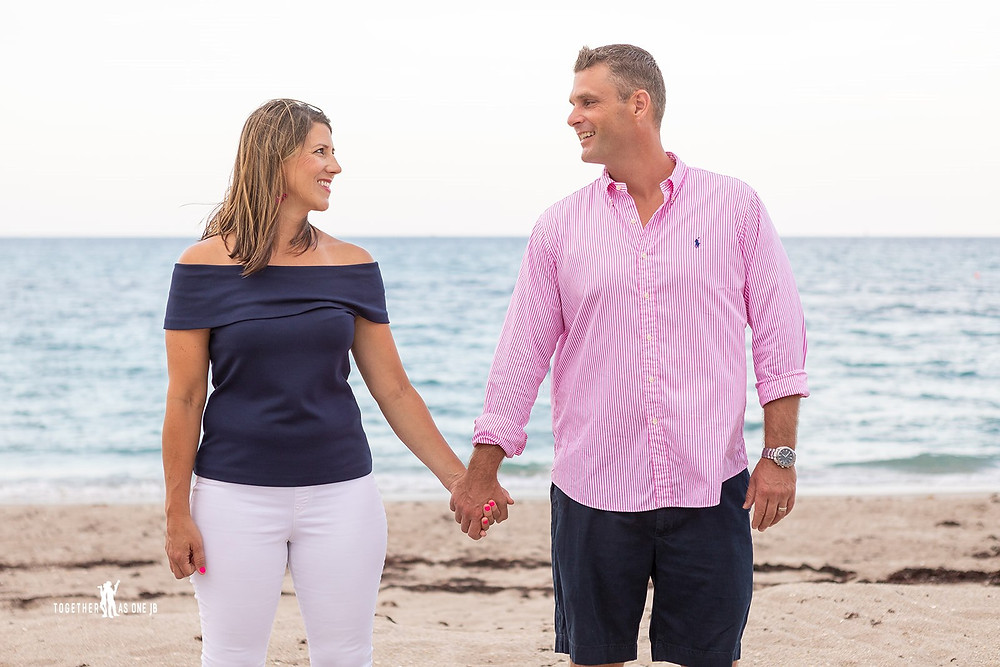 Cincinnati family photographer captures image of husband and wife holding hands in the beach smiling at each other.