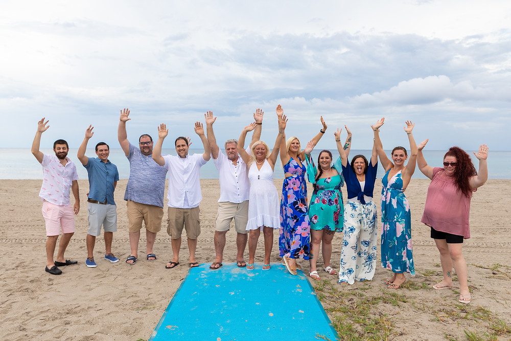 Cincinnati family photographer captures image of family smiling with their hands up posing for a picture in the beach.