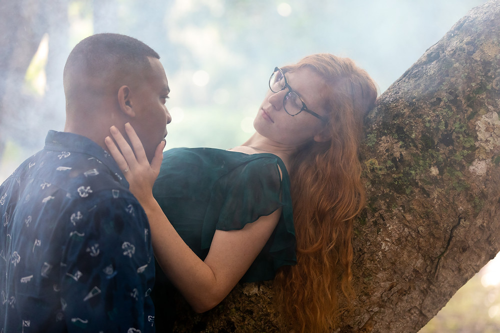 Miami wedding photographer captures image of wife leaning in tree holding husband's face in smoke.
