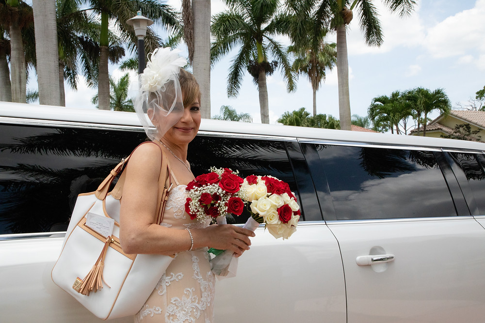 Miami wedding photographer captures image of bride in front of a limousine holding a bouquet of flowers under palm trees.