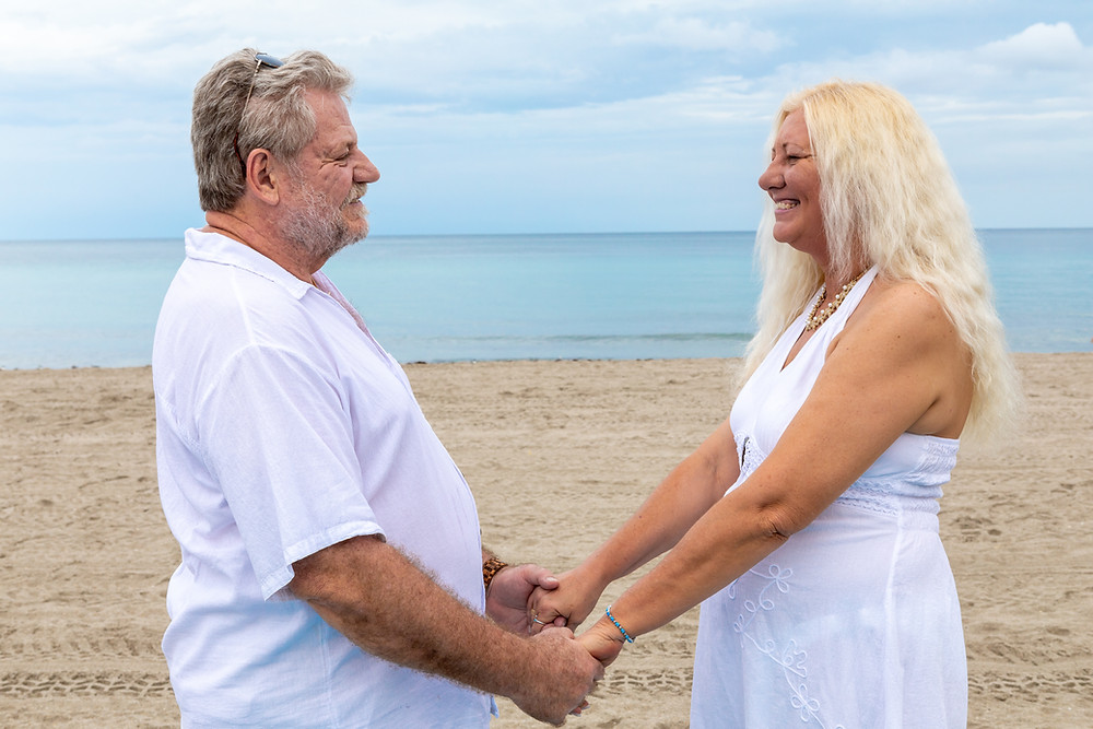 Cincinnati wedding photographer captures image of elder husband and wife in the beach holding hands smiling at each other.