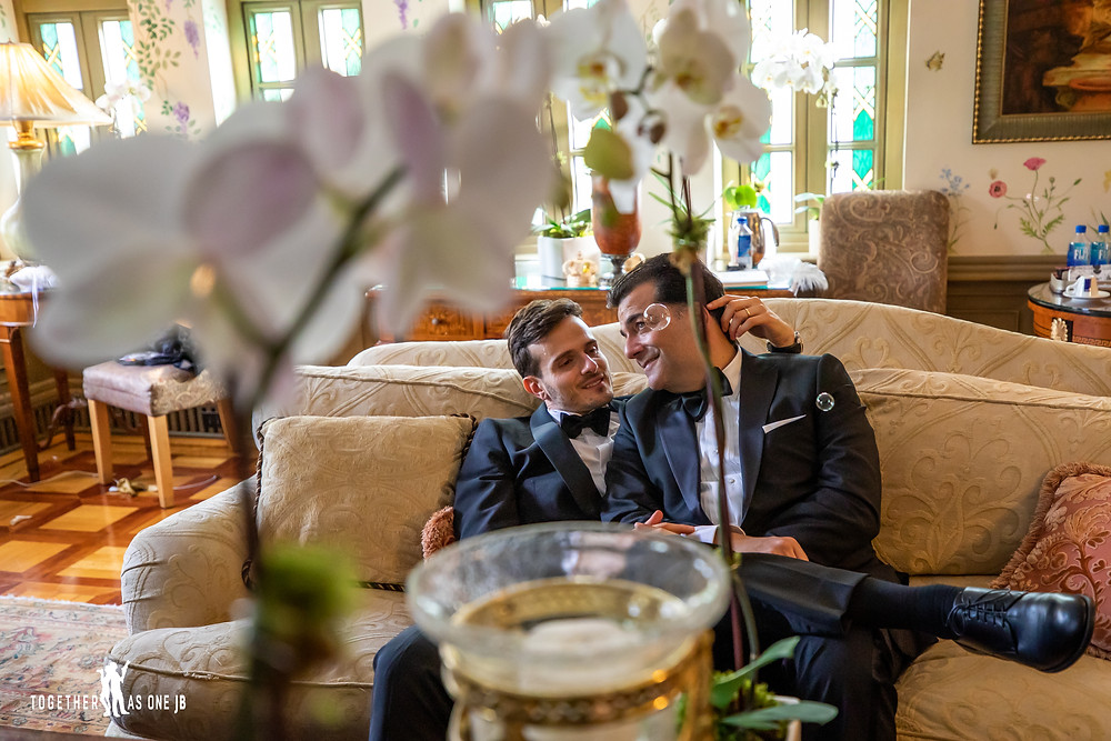 Grooms sit on couch with white orchids framing them with bubbles floating in air
