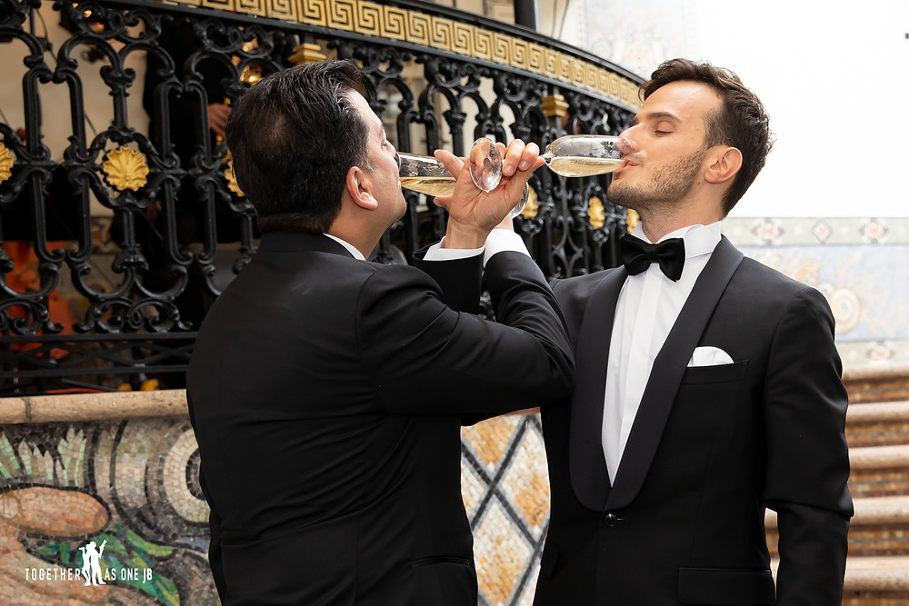 Grooms drinking first glass of champagne as wedding couple