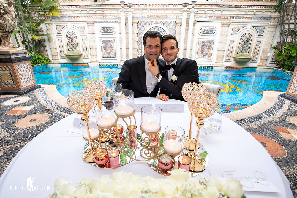Grooms sitting at their wedding table in front of former Versace Mansion pool