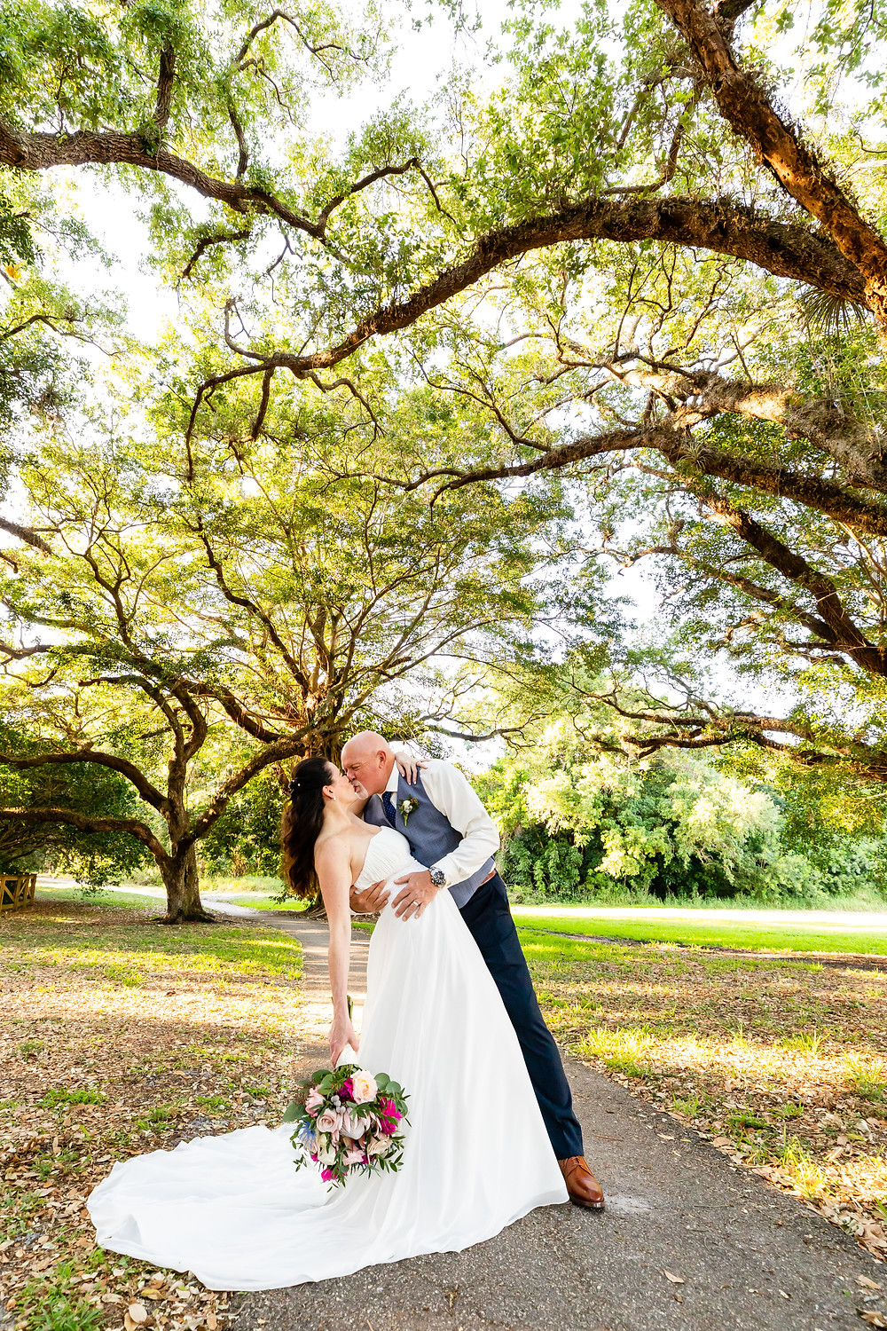 Cincinnati wedding photographer captures image of husband and wife kissing under trees in the park.