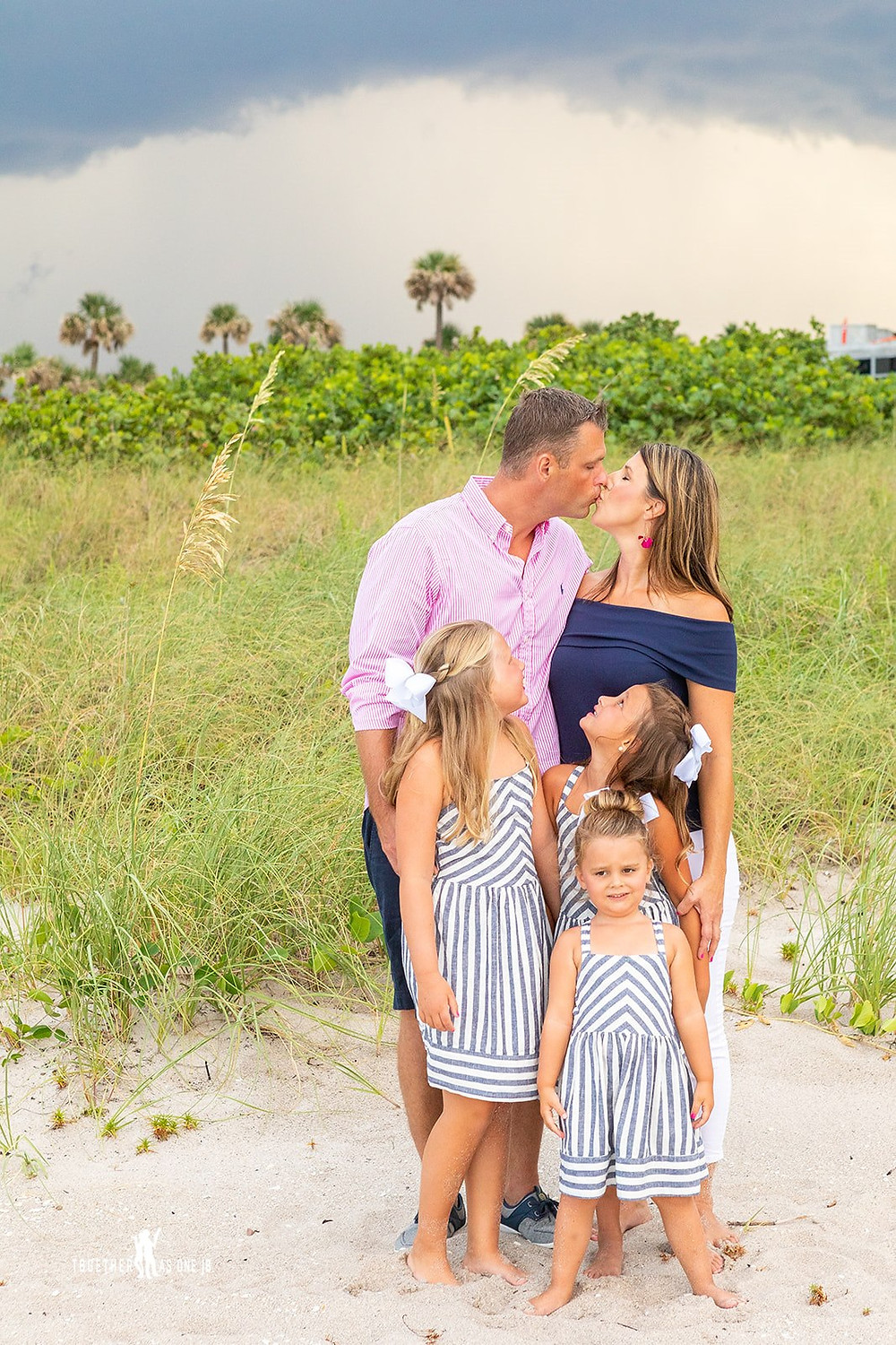 Cincinnati wedding photographer captures image of family posing for a picture on the beach.