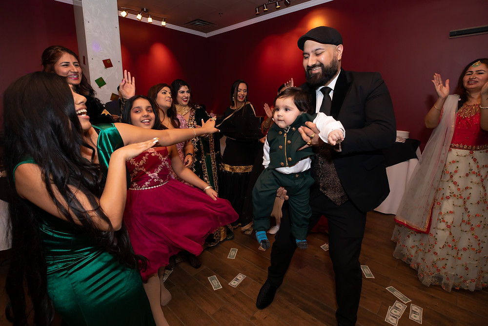 Indian birthday photographer captures image of indian father dancing with baby son and family in lohri birthday.