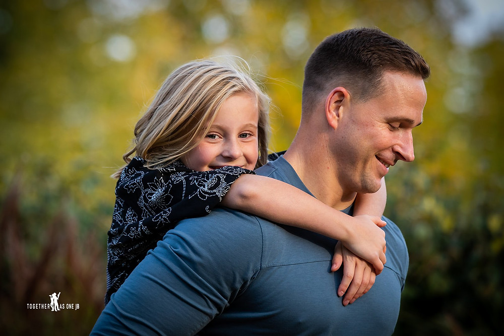 Cincinnati family photographer captures photography of father carrying daughter on his back smiling.