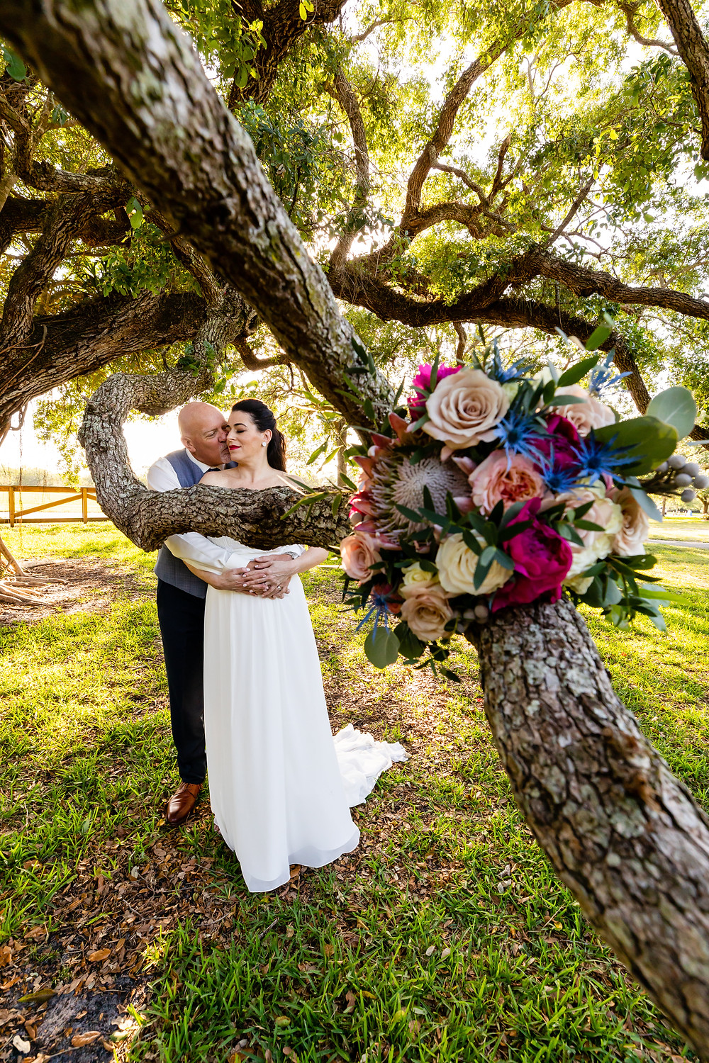 Cincinnati wedding photographer captures image of husband and wife hugging each other kissing with a bouquet of flowers among the trees in the park.