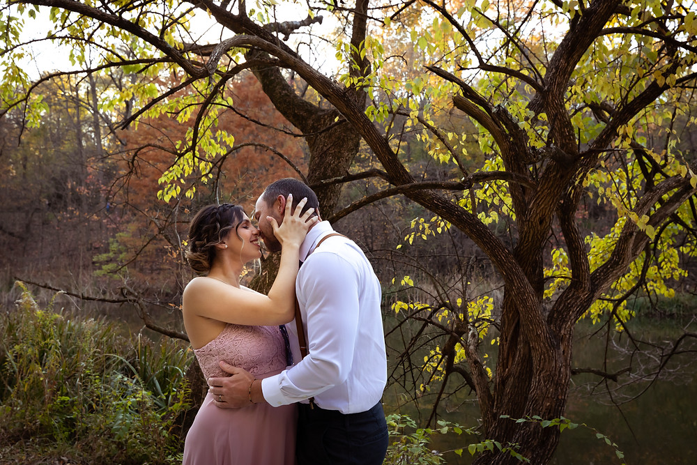 Cincinnati wedding photographer captures image of groom and bride hugging and kissing in forest