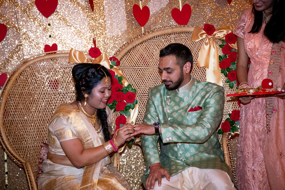 Indian wedding photographer captures image of indian wife putting ring on indian husband's finger.