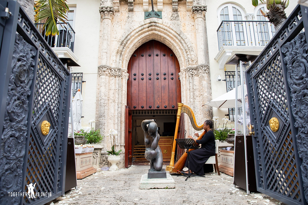 Harp playing by the front gates while wedding guests arrive to wedding venue