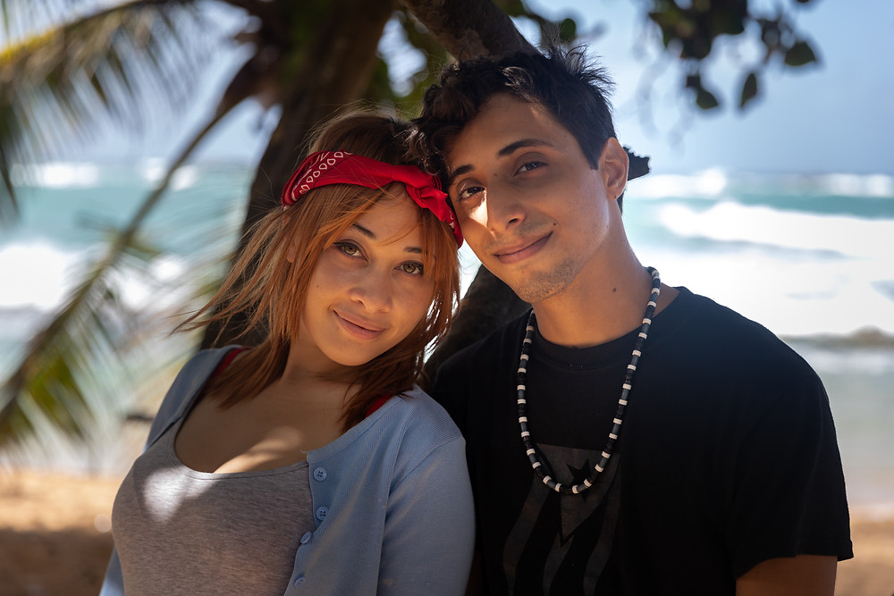Destination photographer captures image of man and woman smiling for a picture with a palm tree in the beach.