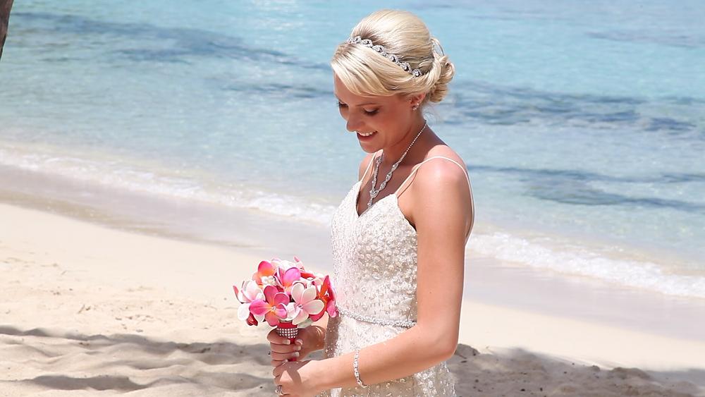 Cincinnati wedding photographer captures image of bride holding bouquet of flowers smiling in the beach.