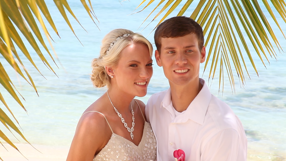 Cincinnati wedding photographer captures image of husband and wife smiling for a picture under a palm tree in the beach.