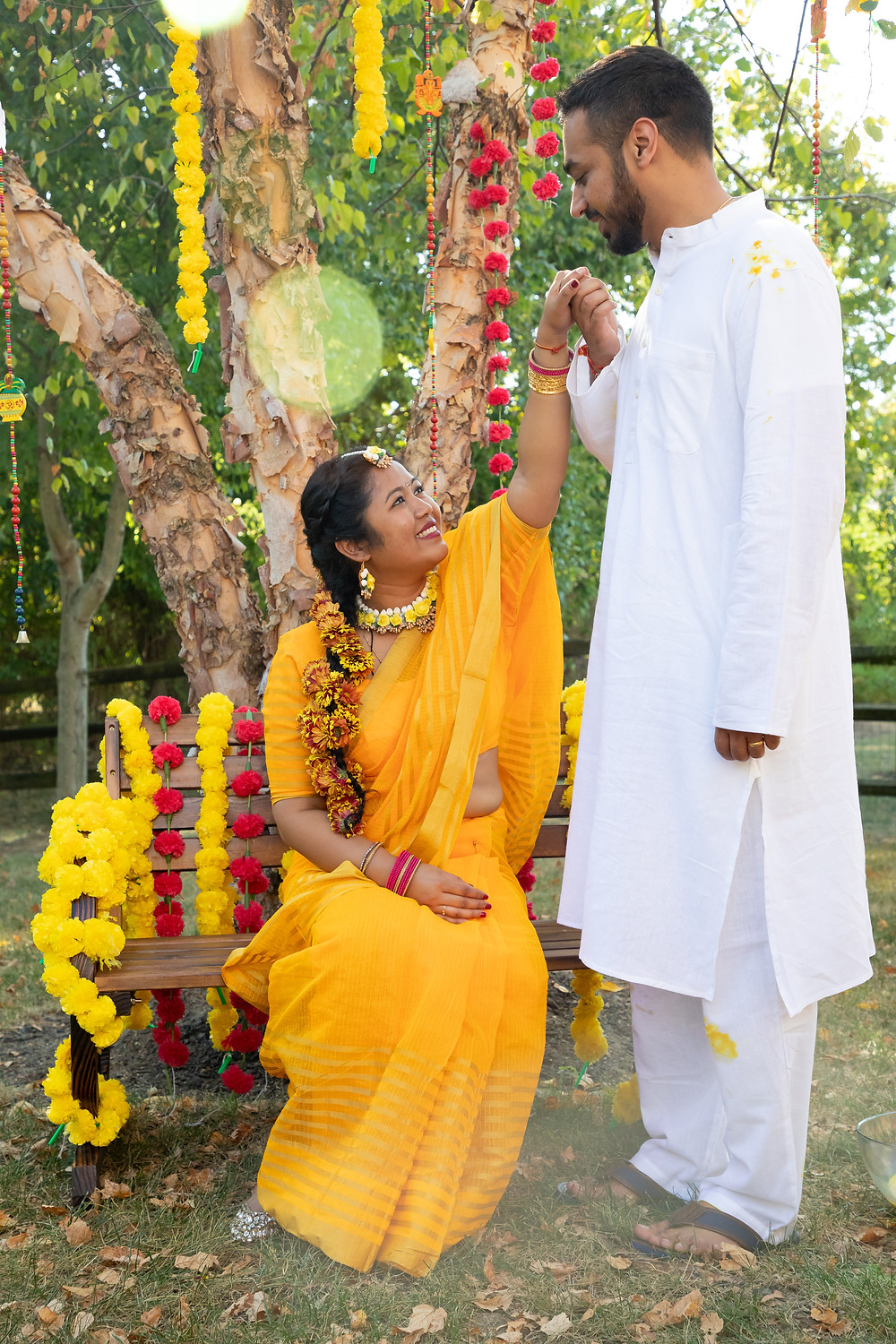 Indian wedding photographer captures image of indian husband smiling and holding wife's hand .