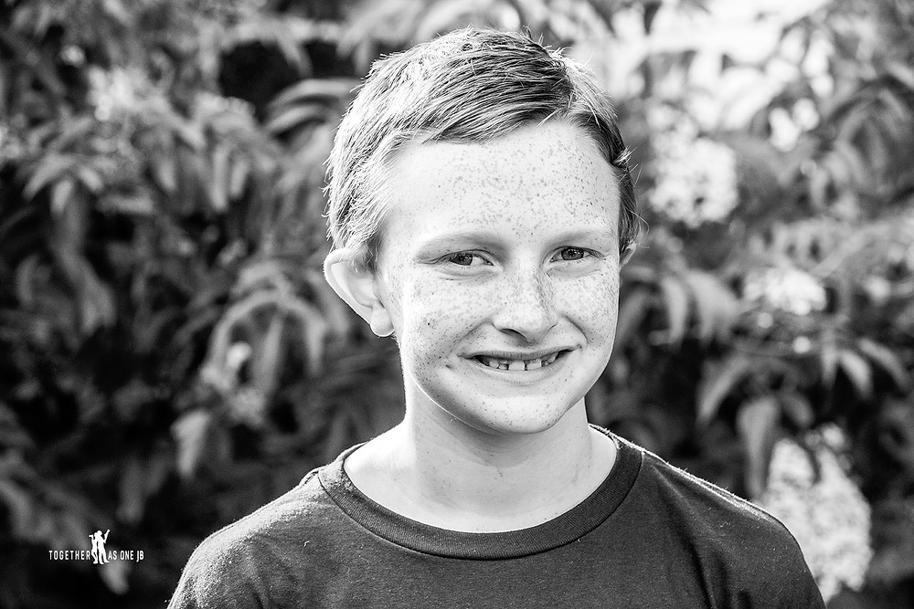 Cincinnati family photographer captures black and white portrait of d smiling boy with freckles in yard.