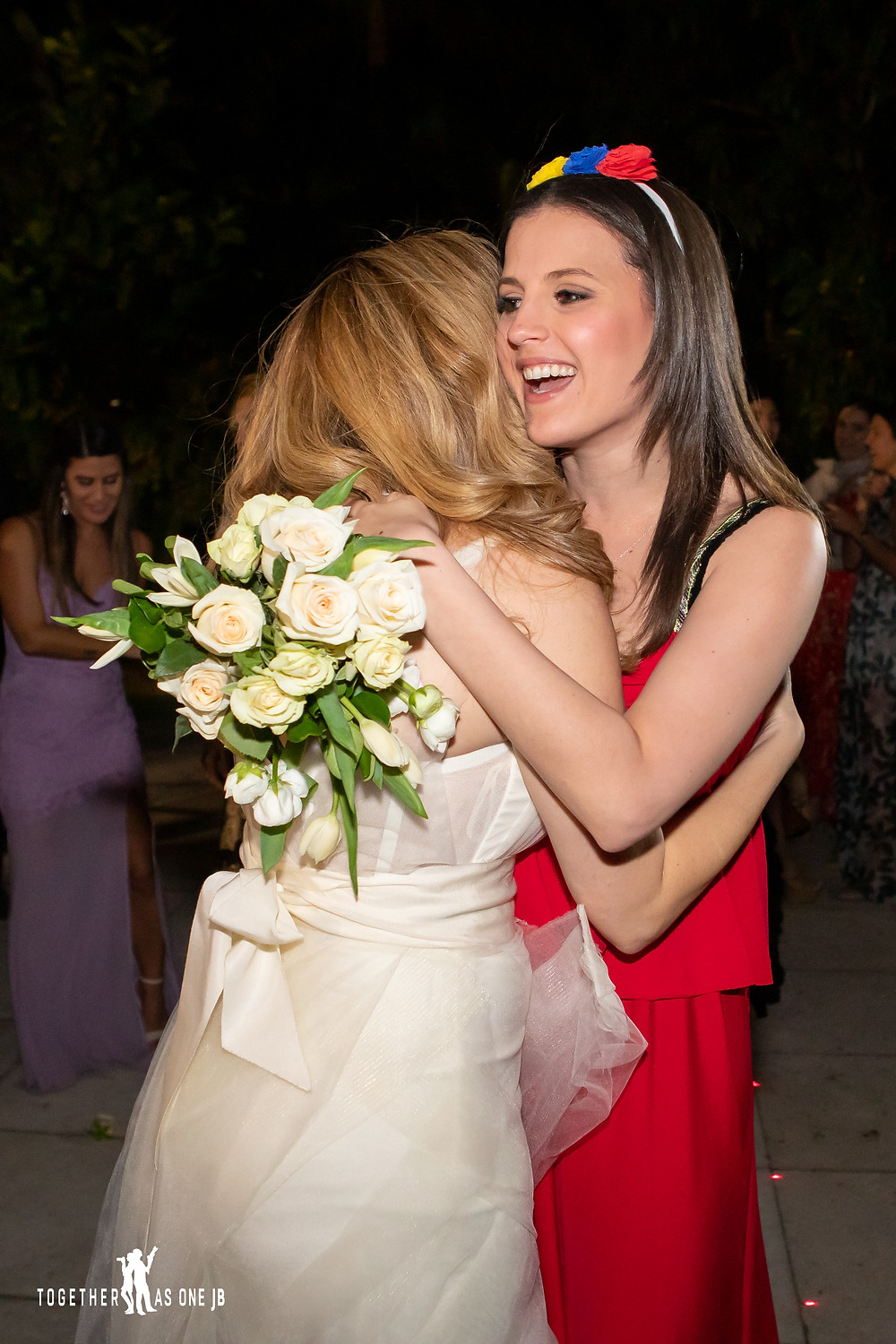 Bride hugs single girl who caught wedding bouquet during wedding reception at the M Building in Wynwood