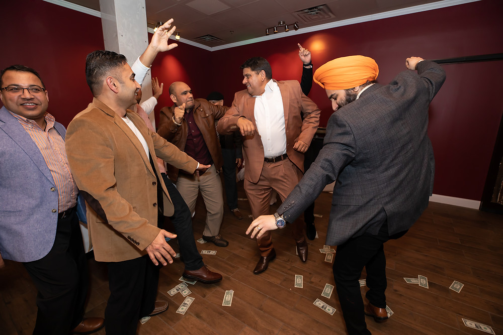 Indian birthday photographer captures image of indian men dancing around money on lohri celebration.