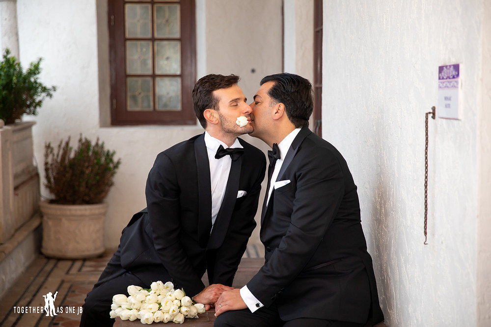 Groom holds white rose in mouth and other groom bites it at the Villa Casa Casuarina