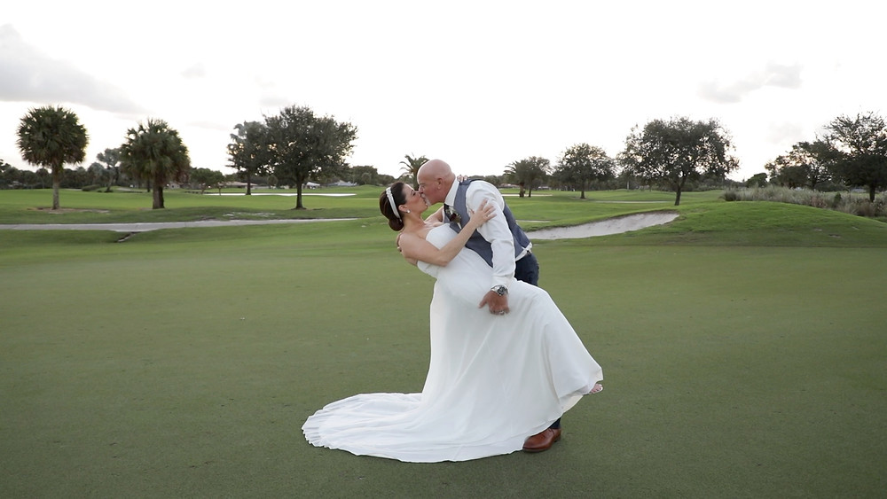 Cincinnati wedding photographer captures image of married couple posing for a picture in a golf field.