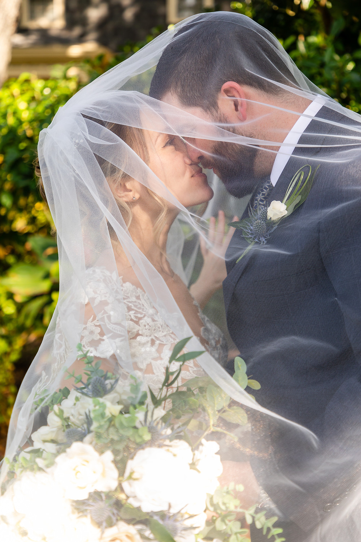 Cincinnatti wedding photographer captures image of man and woman kissing under veil.