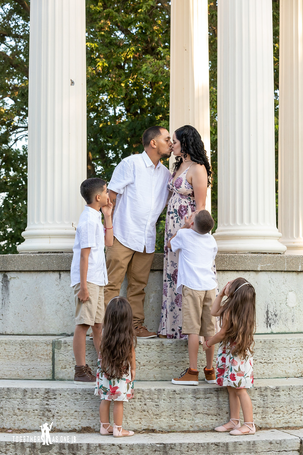 Family Portrait kids looking at mom and pop kissing under the pillars of Mount Snow, Cincinnati Ohio.  Photo taken by Together As One JB to capture the moment of all the kids looking at the parents kissing during their engagement session.