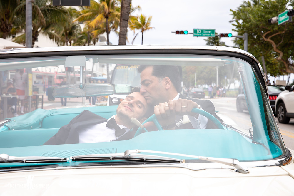 Groom kisses grooms head while sitting in cuban car on busy Miami Ocean Drive