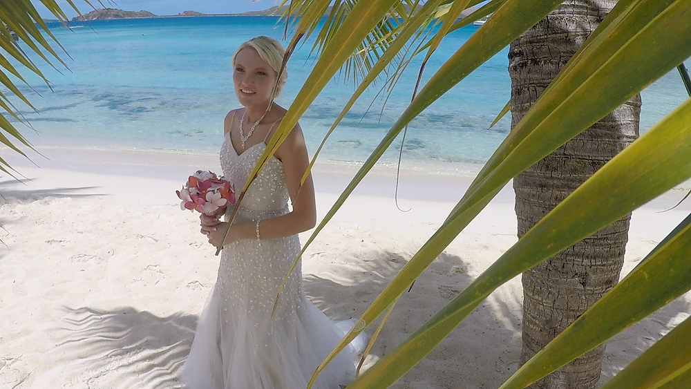 Cincinnati wedding photographer captures image of wife holding bouquet of flowers under a palm in the beach.