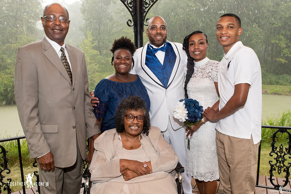 Family group photo of a small wedding in a gazebo while it pours down rain at Mt. Airy Cincinnati Ohio park