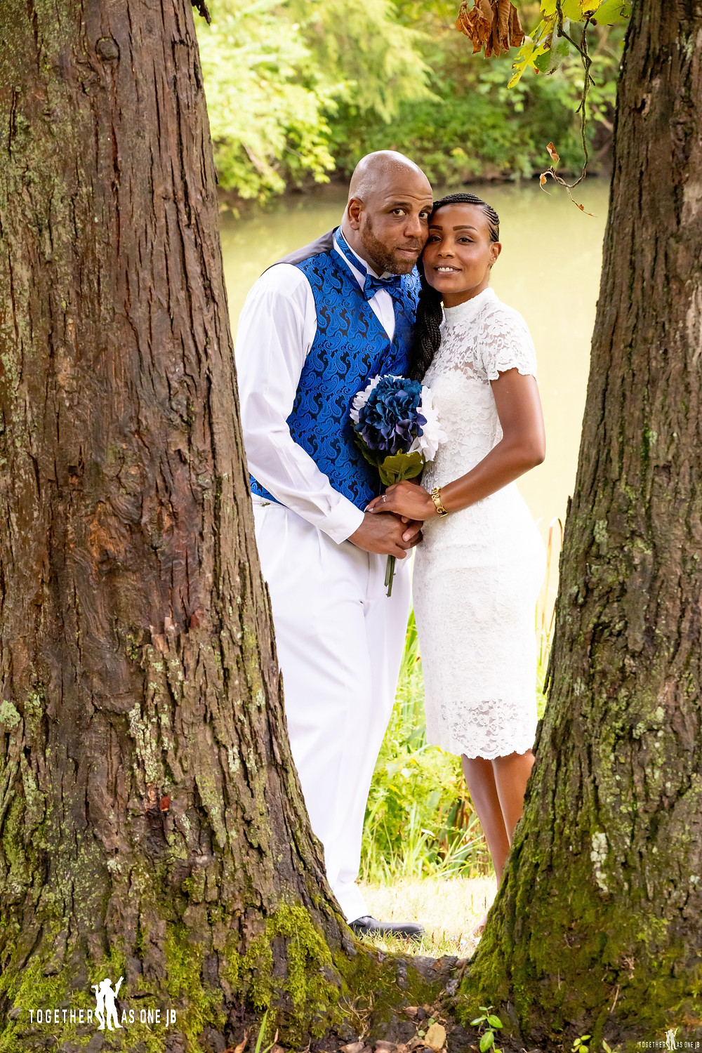 Wedding couple peeking through tree after small intimate wedding in Mt. Airy park