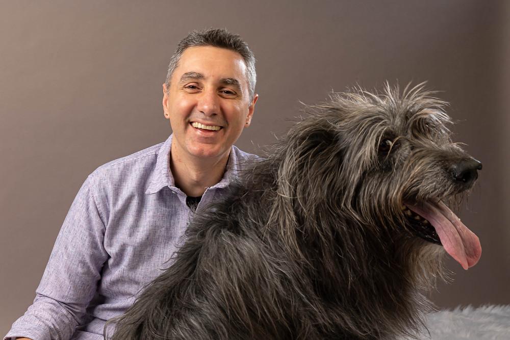 Cincinnati portrait photographer captures image of man smiling hugging furry black dog.