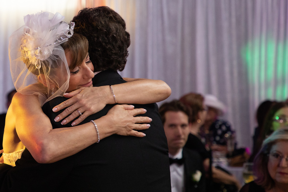 Miami wedding photographer captures image of bride with veil hugging husband.