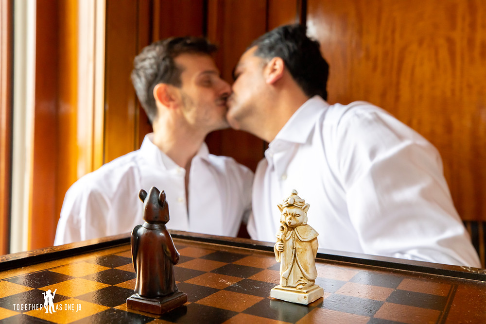 Grooms kissing behind chess pieces