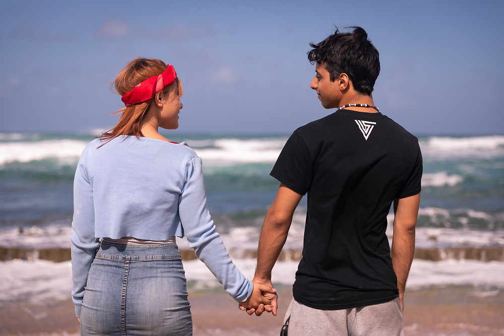 Destination photographer captures image of man and woman looking at each other holding hands in the beach over the horizon.
