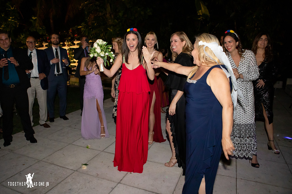 Single ladies catch wedding bouquet at the wedding reception in the M Building in Wynwood