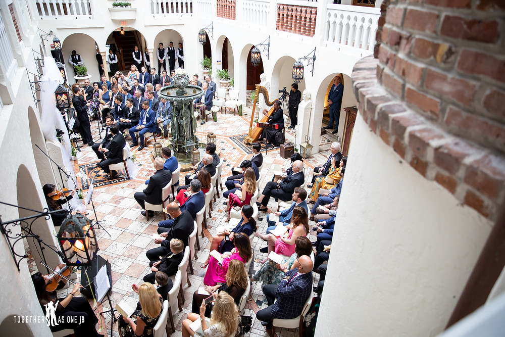 Wedding guests and couple seated listening to orchestra during wedding ceremony in outside courtyard at the Villa Casa Casuarina