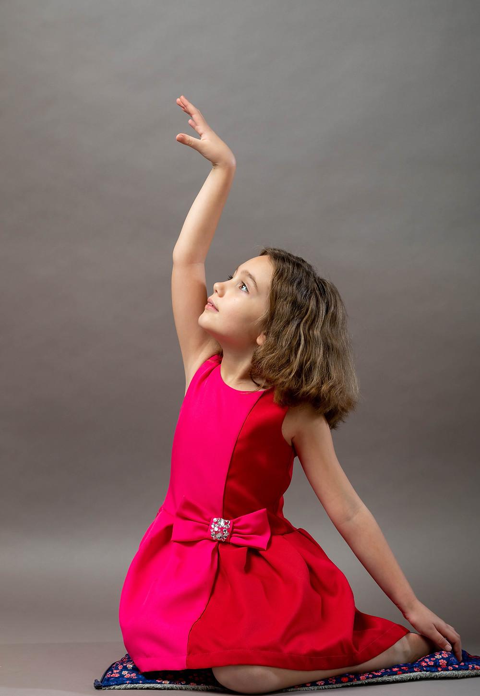 Cincinnati portrait photographer captures girl with red dress sitting on floor elegantly posing with her hand up.