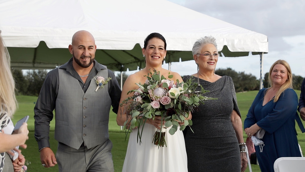 Cincinnati wedding photographer captures image of bride with a bouquet of flowers posing for a picture with family members.