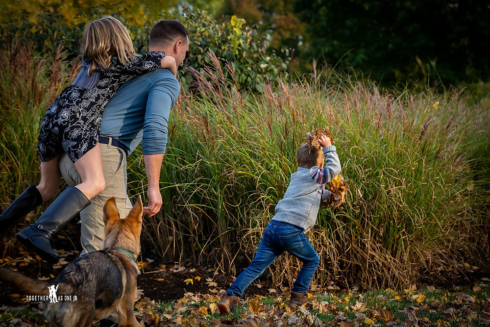 Cincinnati family photographer captures children playing in yard with a dog.